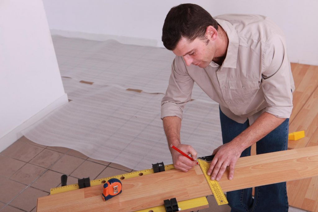 male worker putting a markings on the wood