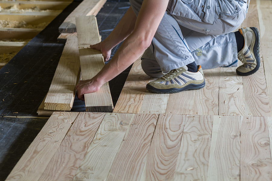 professional carpenter installing natural wooden new planks on wooden frame floor in empty unfinished room under reconstruction.